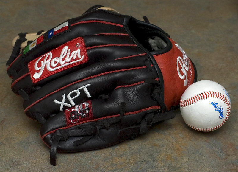 Close up of a baseball and a black baseball glove.